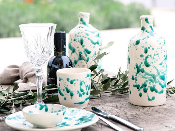 Detail van groen Italiaans servies met glazen en olijffles